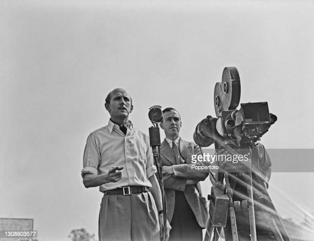 English filmmaker Michael Powell stands on left with cinematographer Ronald Neame to instruct actors on direction prior to shooting a scene for the...