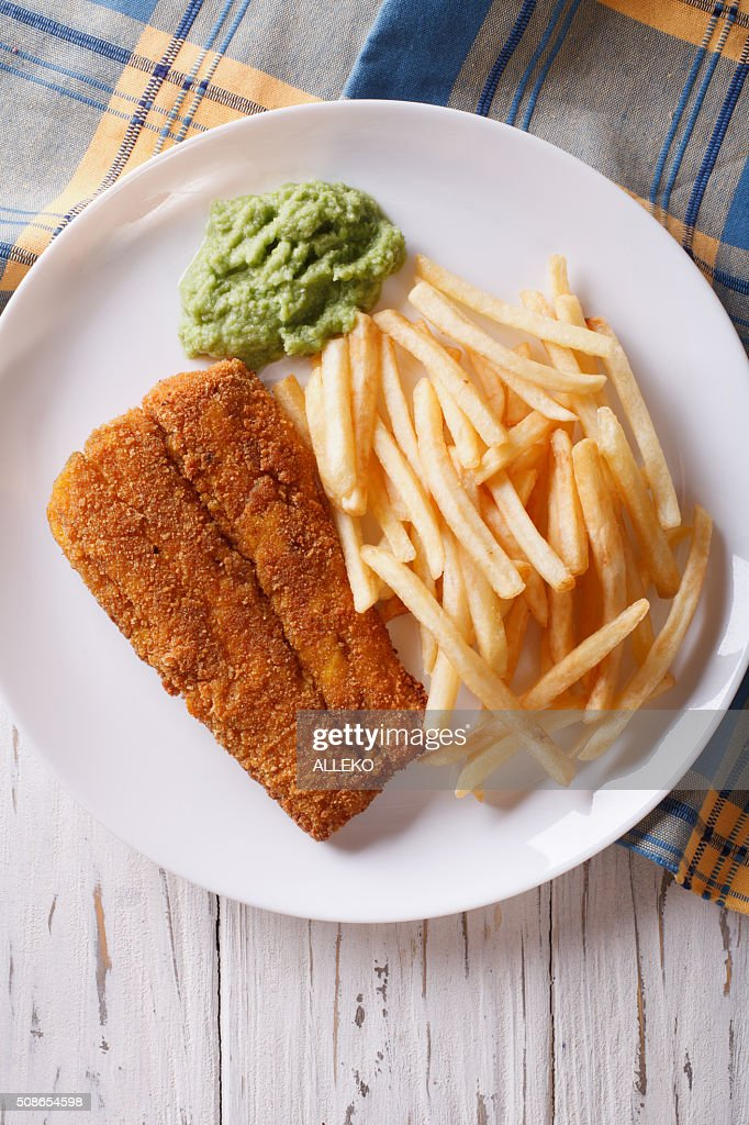 English food: fried fish in batter with chips close-up. vertical : Stock Photo