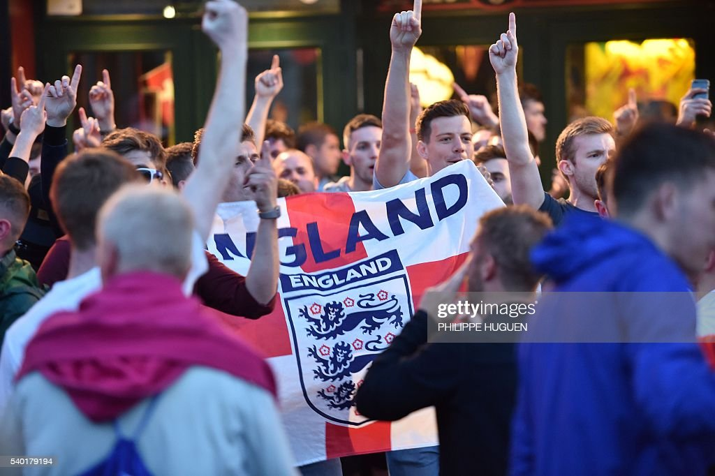 English football fans drink beer at the terrace of a bar in Lille, northern France, on June 14, 2016. The bars in downtown Lille will be closed 'at midnight' on June 15 and 16, on the sidelines of the Euro 2016 football tournament matches Russia vs Slovakia in Lille and England vs Wales in Lens, has announced on June 14, 2016 the Prefect of the Nord region, Michel Laland. / AFP / PHILIPPE