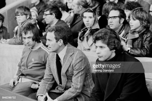 English football manager of Queens Park Rangers Dave Sexton sits on a bench while following a game against Chelsea FC with some members of his team...