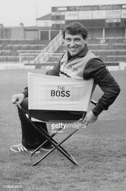 English football player, manager, pundit and chairman of Watford Football Club Graham Taylor sitting on a chair which says 'The Boss', at Vicarage...