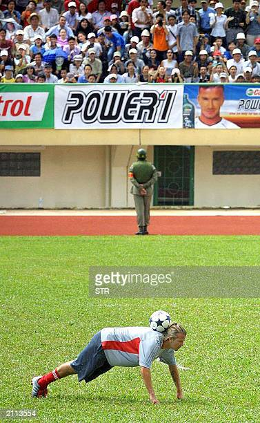 English football star player David Beckham demonstrates his skills as a soldier on duty keeps an vigil eye on Vietnamese fans 25 June 2003 at the...
