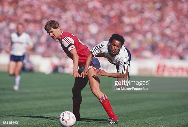 English footballer and captain of Arsenal Tony Adams shields the ball from Luton Town player Mark Stein during the 1988 Football League Cup Final...