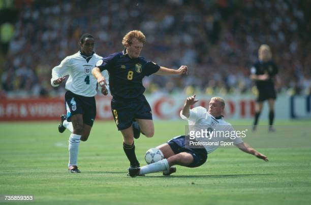 English footballer and midfielder with the England national team Paul Gascoigne dives to tackle Stuart McCall of Scotland for the ball as fellow...