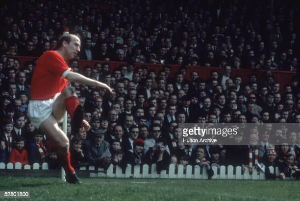 English footballer Bobby Charlton taking a corner for Manchester United, 1968.