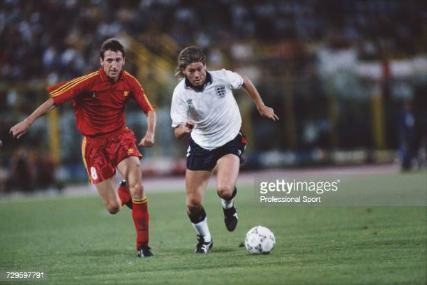 English footballer Chris Waddle runs with the ball as Belgium midfielder Franky Van der Elst chases during the Round of 16 match between England and...