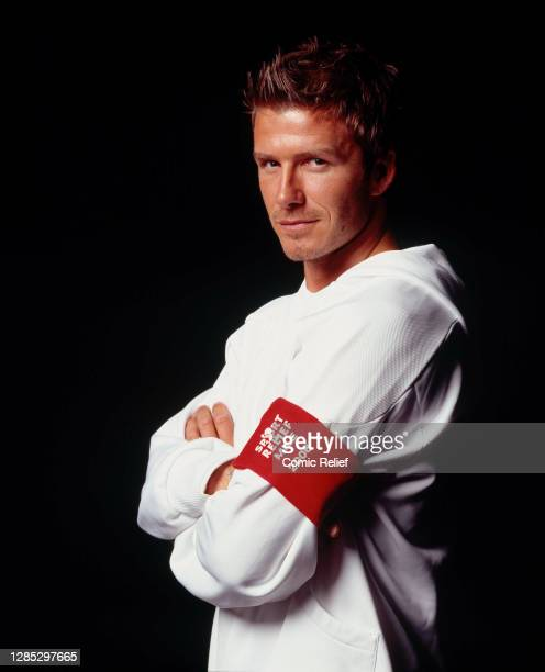 English footballer, David Beckham, looks at the camera whilst wearing the sport relief red sock as a captain's arm band for sport relief 2006 in...