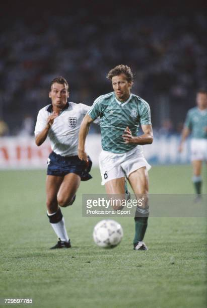 English footballer David Platt attempts to catch and stop West Germany player Guido Buchwald during the semi final match between West Germany and...