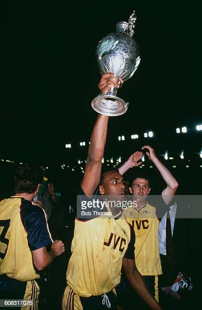 English footballer David Rocastle of Arsenal holds up the championship trophy after his team beat Liverpool 20 at Anfield to win the Football League...