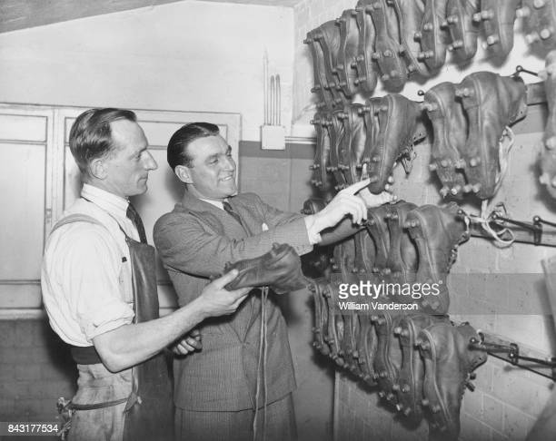 English footballer Eddie Hapgood captain of Arsenal FC discusses football boots with 'Cobbler' Lee the team's shoemaker at Highbury London 22nd...