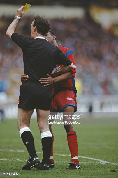 English footballer Ian Wright of Crystal Palace appeals to referee George Courtney as a yellow card is raised for a booking during the 1991 Full...