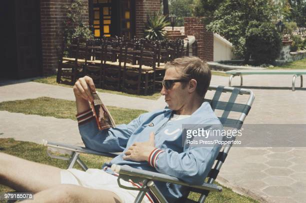 English footballer Jack Charlton of the England national football team squad relaxes with a 'Hondo' western paperback book in the grounds of the...