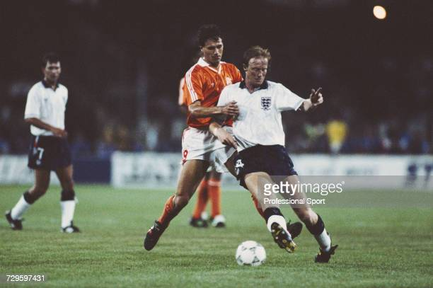 English footballer Mark Wright is tackled by Marco van Basten of the Netherlands as England captain Bryan Robson looks on in the Group F match...
