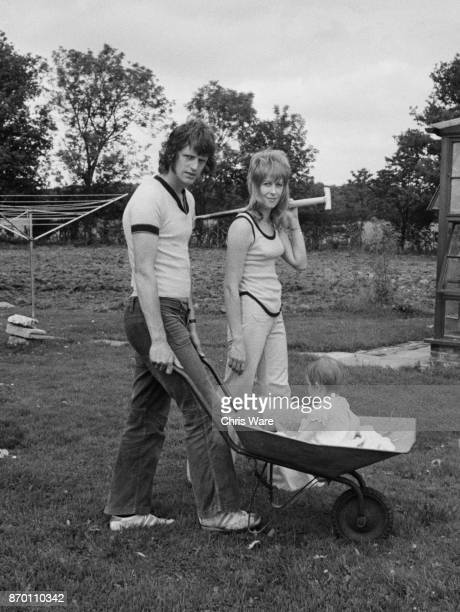 English footballer Mike Channon and his wife Jane push their baby daughter Nicola in a wheelbarrow while working on their farm, UK, August 1973.
