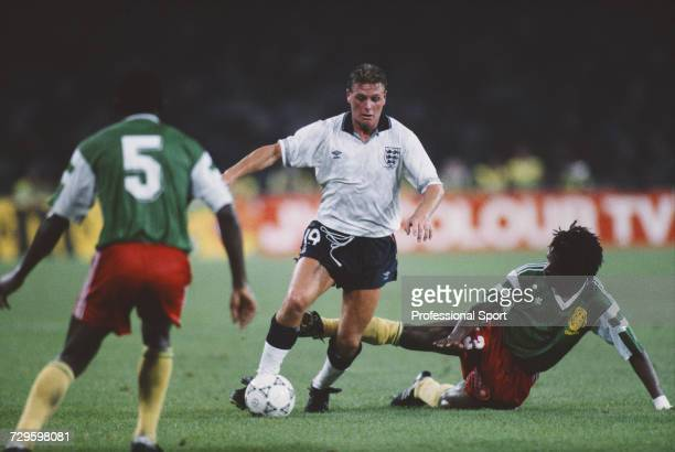 English footballer Paul Gascoigne makes a run with the ball between Bertin Ebwelle on left and JeanClaude Pagal on right in the quarter final match...