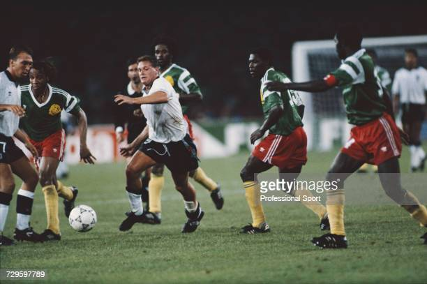 English footballer Paul Gascoigne makes a run with the ball past various Cameroon players as teammate David Platt looks on in the quarter final match...