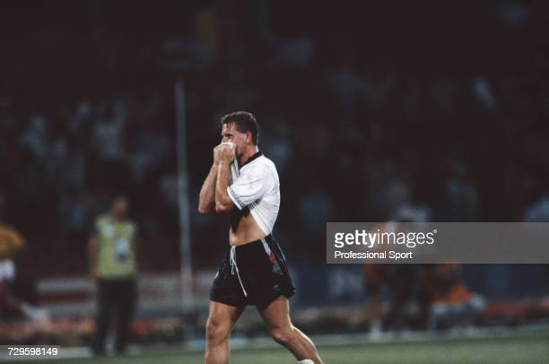 English footballer Paul Gascoigne wipes his face with his shirt during play in the quarter final match between Cameroon and England in the 1990 FIFA...