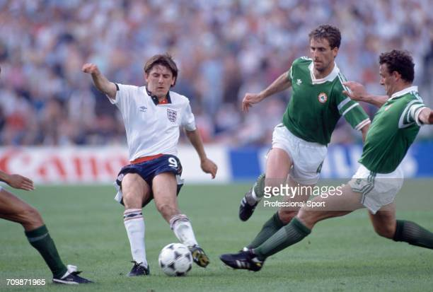 English footballer Peter Beardsley is tackled for the ball by Republic of Ireland players Kevin Moran and Mick McCarthy during play in the group 2...
