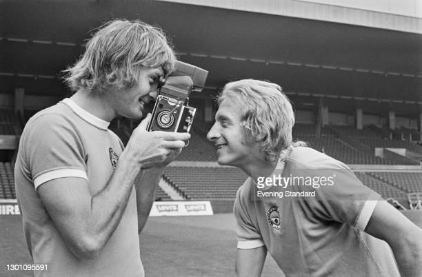 English footballer Rodney Marsh of Manchester City FC films team-mate Denis Law at the start of the 1973-74 football season, UK, 30th August 1973.