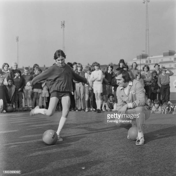 English footballer Terry Cooper of Leeds United watches young Joan Williams show her skills with the ball, UK, 27th October 1972.
