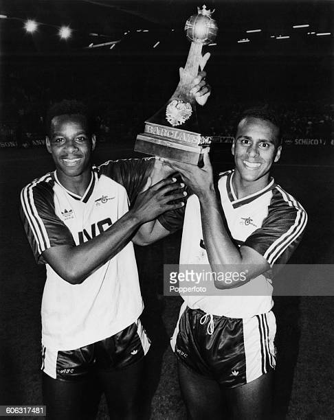 English footballers Michael Thomas and David Rocastle of Arsenal FC holding up the trophy after their team beat Liverpool FC at Anfield to win the...