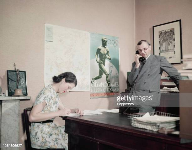 English former athlete Sandy Duncan general secretary at the British Olympic Association takes a telephone call as a secretary takes notes in the...