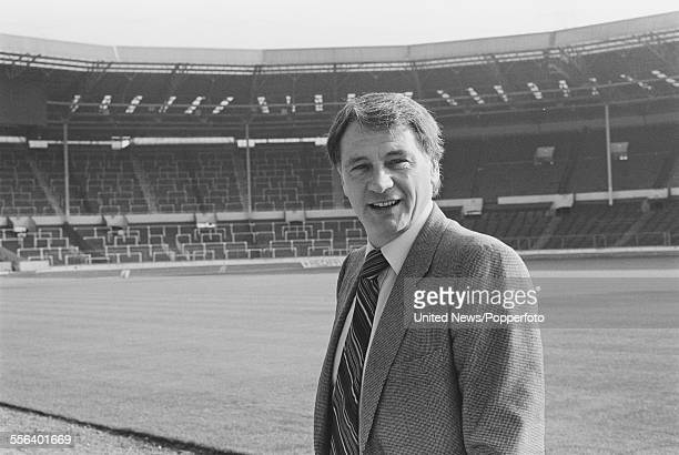 English former footballer and manager of the England national football team Bobby Robson pictured standing beside the pitch at Wembley stadium in...