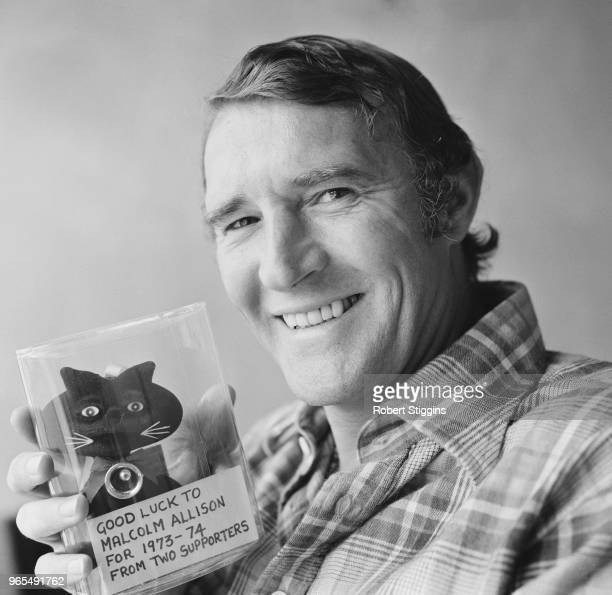 English former footballer and recently appointed manager of Crystal Palace FC, Malcolm Allison pictured holding a feline shaped good luck momento for...