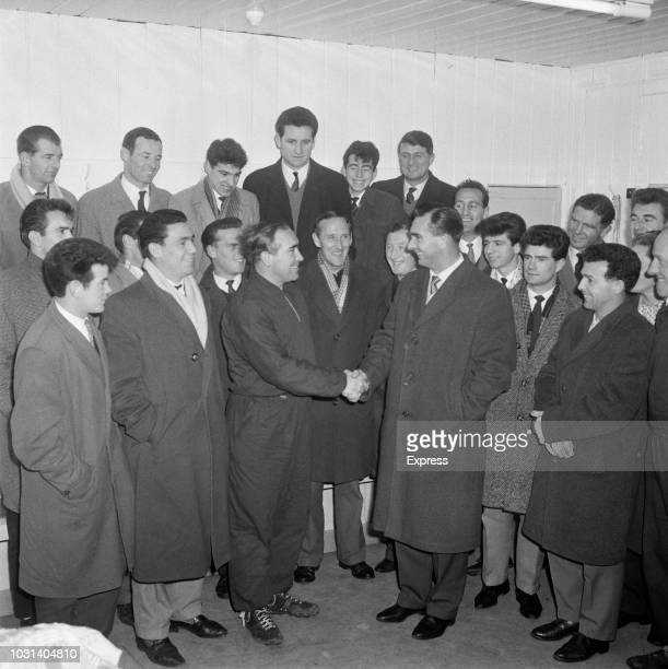 English former footballer Jackie Milburn new manager of Ipswich Town FC pictured on right shaking hands with departing manager Alf Ramsey as members...