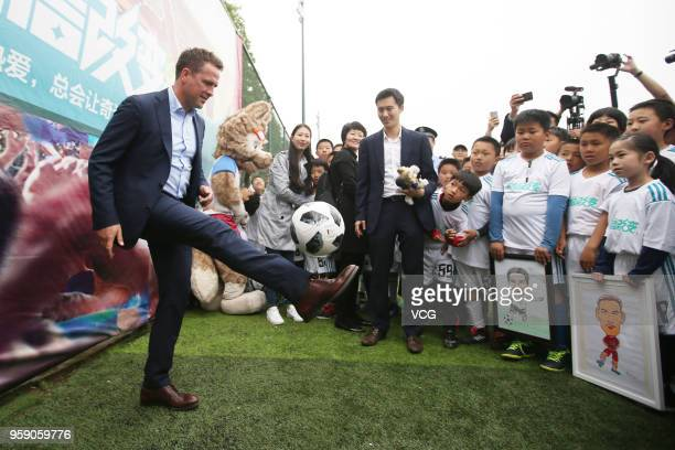 English former footballer Michael Owen kicks a ball during Hisense 'Road to Russia' FIFA World Cup event on May 15, 2018 in Qingdao, Shandong...