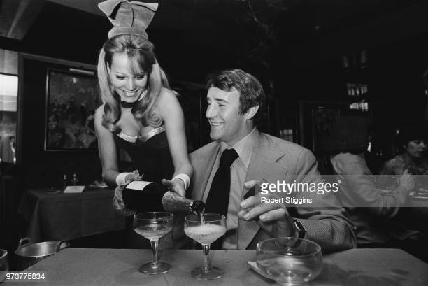English former soccer player and manager of Crystal Palace FC Malcolm Allison smoking a cigar while a Playboy Bunny serves him some wine London UK...