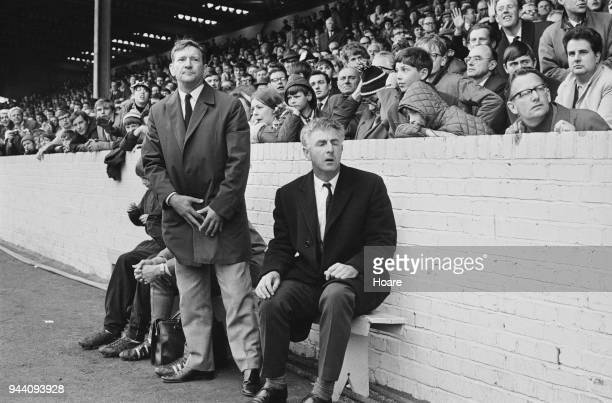 English former soccer player and manager of Queens Park Rangers FC Alec Stock and English trainer Bill Dodgin Jr watch match from touchline UK 13th...