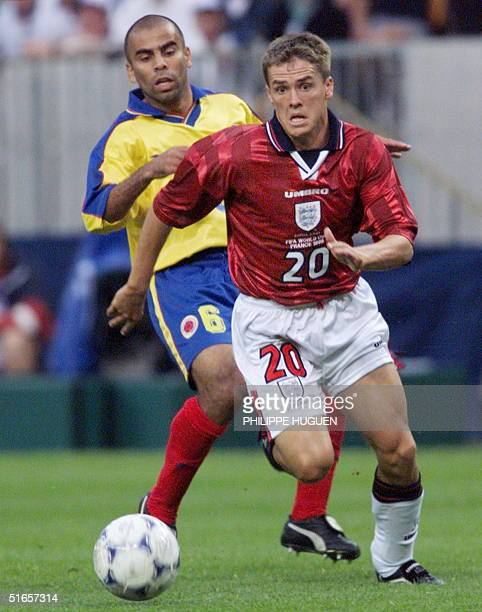 English forward Michael Owen is chased by Colombian midfielder Mauricio Serna, 26 June at the Felix Bollaert stadium in Lens, northern France, during...