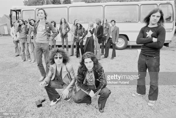 English glam rock group T-Rex and their entourage by their tour bus during a four-date British tour, June 1972. Foreground, left to right: bassist...