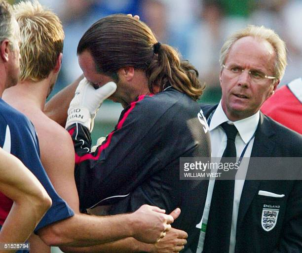 English goalkeeper David Seaman is consolated by his captain midfielder David Beckham as their coach Swedish Sven Goran Eriksson looks on at the end...