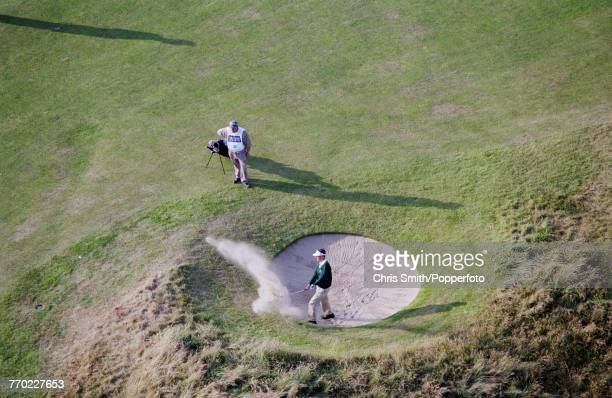 English golfer Daren Lee pictured in action chipping out of a bunker sand trap during competition in the 1998 British Open Championship at the Royal...