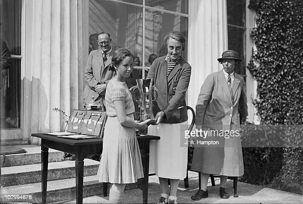 English golfer Enid Wilson presents 13 yearold Nancy Craigmillar Manning Jupp with the Championship Cup after the teenager won the final of the...