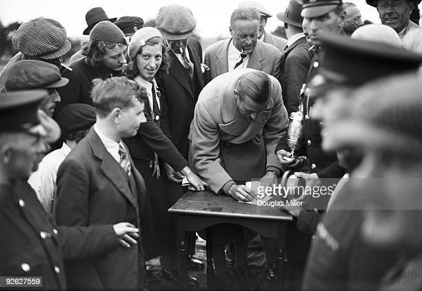 English golfer Henry Cotton signs autographs for fans at the Open Golf Championship, 29th June 1934. Cotton won the championship, which was held at...