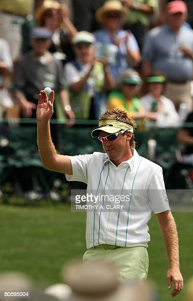 English golfer Ian Poulter acknowledges the gallery after hitting a holeinone on the sixteenth hole during the first round of the US Masters at the...