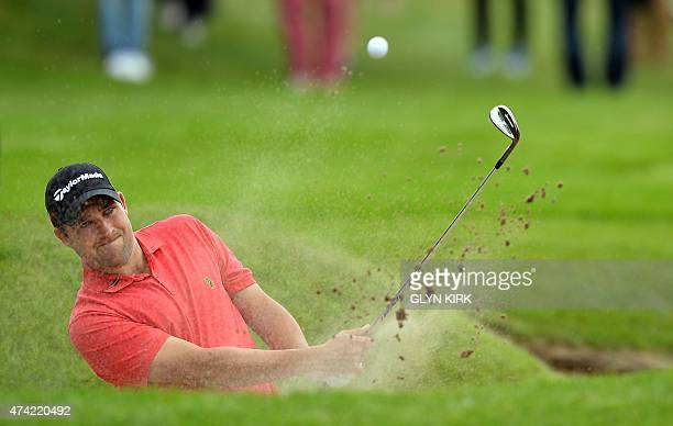 English golfer Jason Barnes plays out of a greenside bunker at the 12th green during the first round of the PGA Championship at Wentworth Golf Club...
