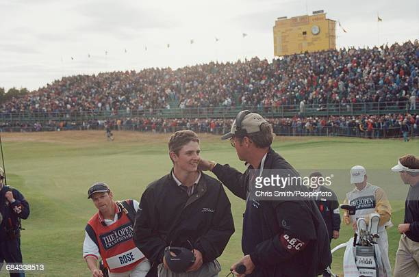 English golfer Justin Rose is congratulated by a member of Popperfoto via Getty Images Sport production staff after walking off the 18th green during...