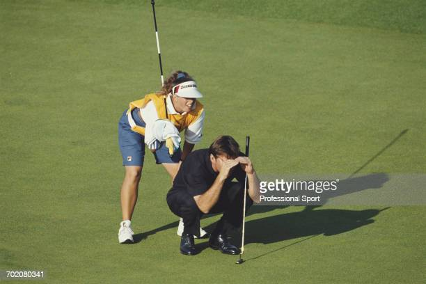 English golfer Nick Faldo pictured crouching down on a green with his caddie Fanny Sunesson to line up a potential shot during play in the 1993 Open...