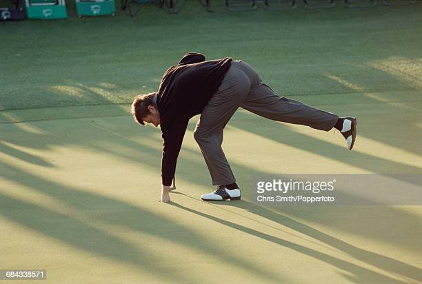 English golfer Nick Faldo pictured retrieving his ball from a hole during competition to miss the cut in the 1998 Masters Tournament at Augusta...
