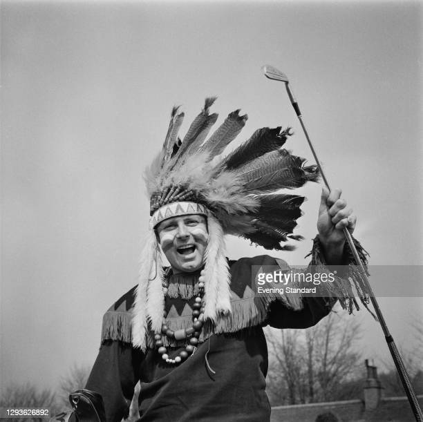English golfer Peter Alliss dressed as a Native American in a feather headdress and bead necklace, UK, April 1968.