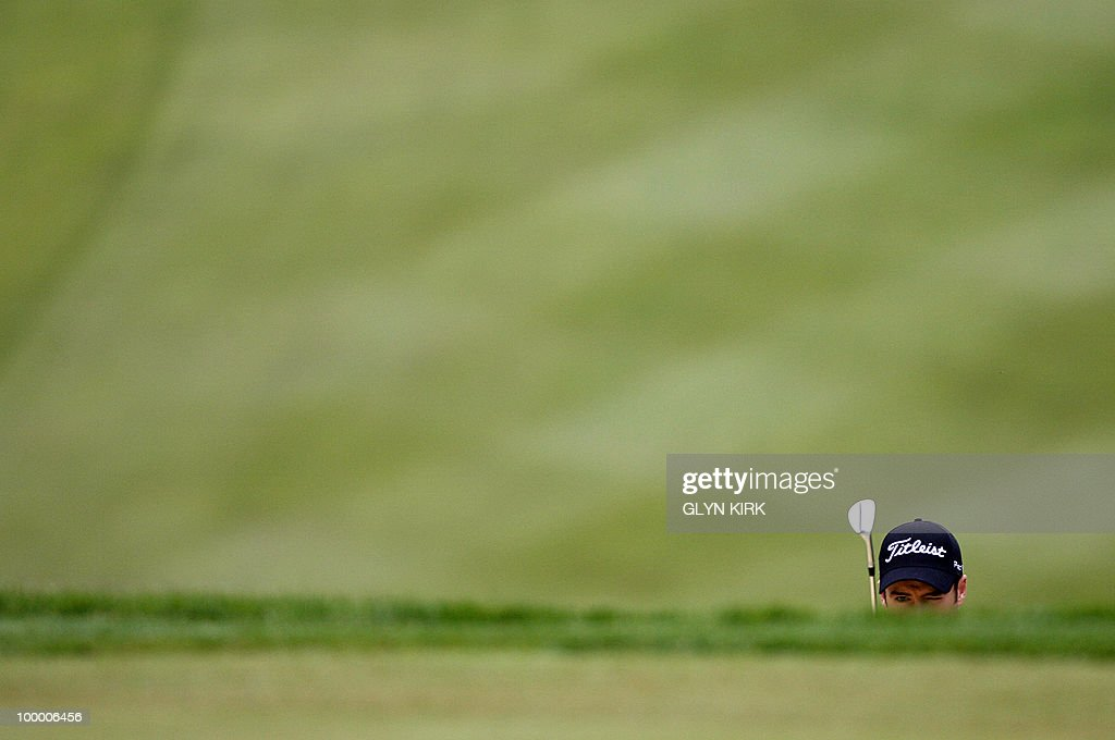 English golfer Ross Fisher prepares to play a bunker shot on the 1st green on the first day of the PGA Championship on the West Course at Wentworth, central England, on May 20, 2010.