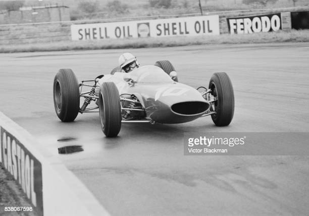 English Grand Prix motorcycle road racer and Formula One driver John Surtees drives the Team Ferrari Ferrari 156 V6 during the British Grand Prix at...