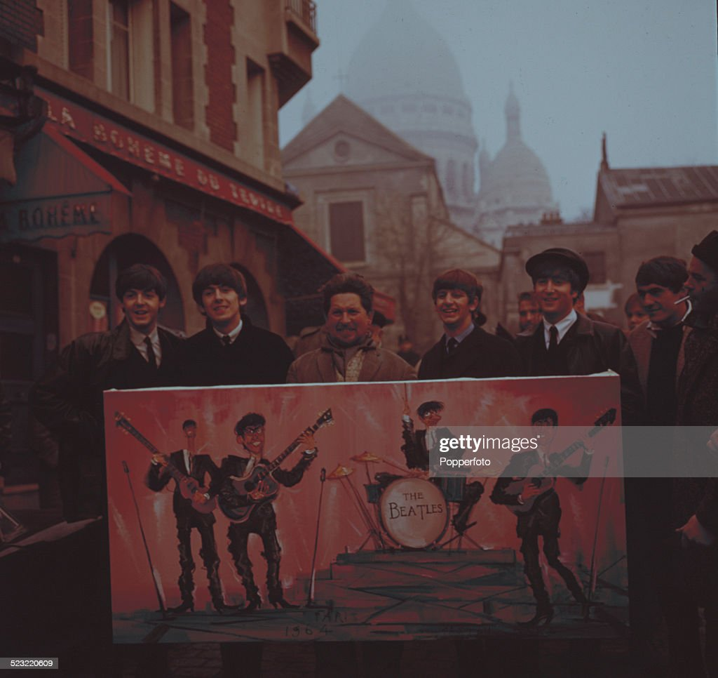 English group The Beatles posed with a street artist holding a painting of the band on a street in Montmartre, Paris in January 1964. From left to right: Paul McCartney, George Harrison (1943-2001), Ringo Starr and John Lennon (1940-1980).