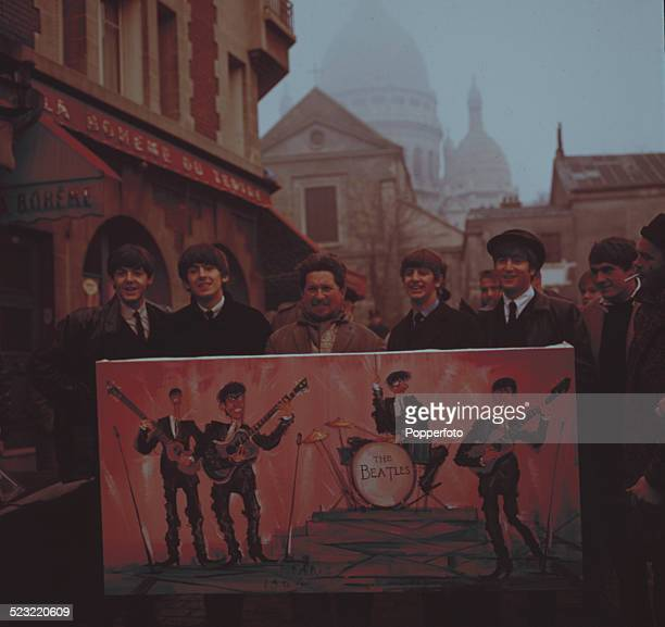 English group The Beatles posed with a street artist holding a painting of the band on a street in Montmartre Paris in January 1964 From left to...