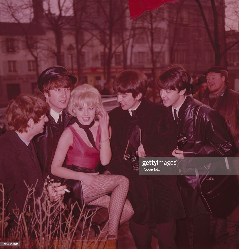 English group The Beatles posed with an unidentified girl in a street in Paris in January 1964. From left to right: Paul McCartney, George Harrison (1943-2001), John Lennon (1940-1980) and Ringo Starr.
