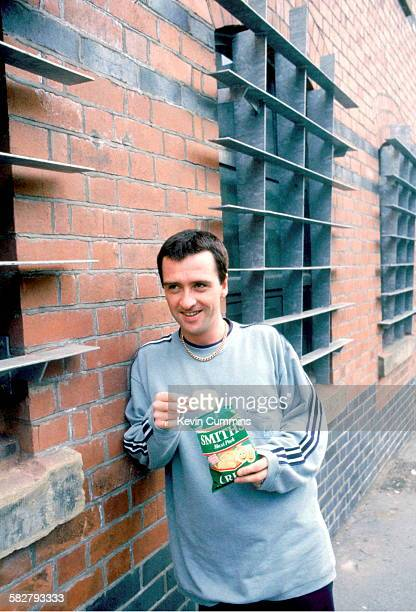 English guitarist and songwriter Johnny Marr eating crisps circa 1990
